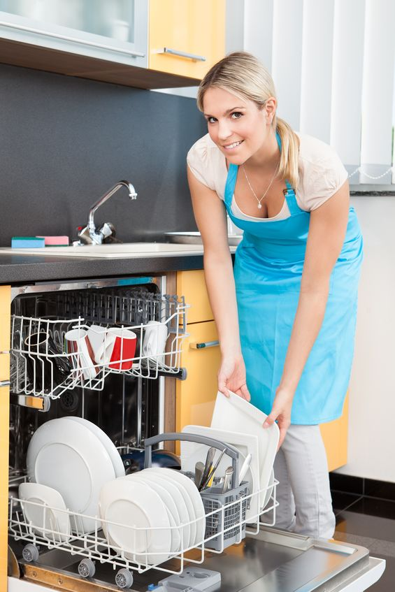 21478032 - happy woman putting utensils in dishwasher for cleaning